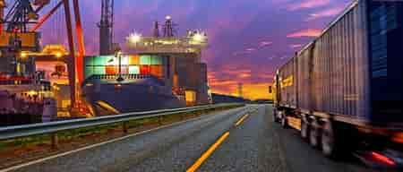 A truck on the road and a freight boat in the distance.